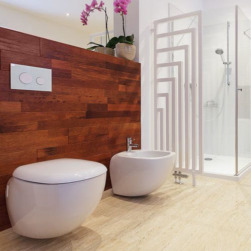 A clean, white bathroom with toilets and a open-air shower. Purple orchids in the background.