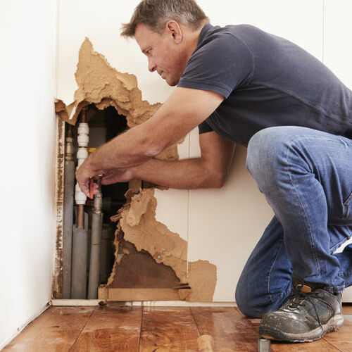 A Plumber Repairs a Pipe in a Wall.