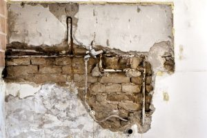 exposed pipes in damaged wall